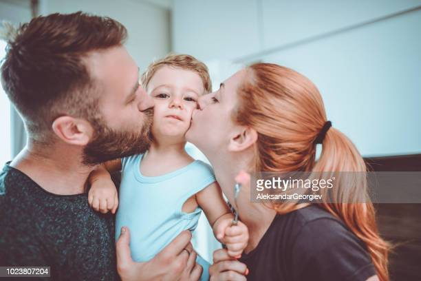parents holding and kissing their baby boy - kissing stock pictures, royalty-free photos & images
