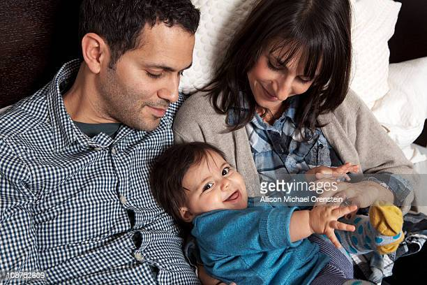 parents holding baby girl in bed - israeli ethnicity stock pictures, royalty-free photos & images