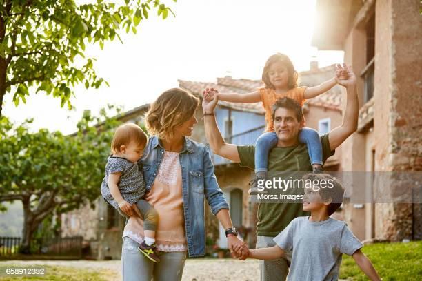 parents holding children while walking on footpath - cena não urbana imagens e fotografias de stock