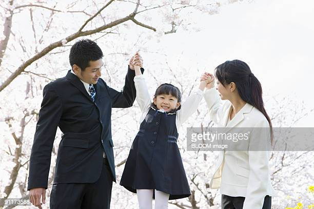 Parents holding daughter up by hands