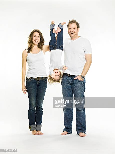 Parents holding daughter upside down