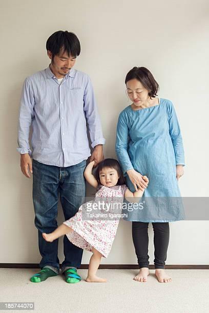 Parents holding daughter's hands,  portrait
