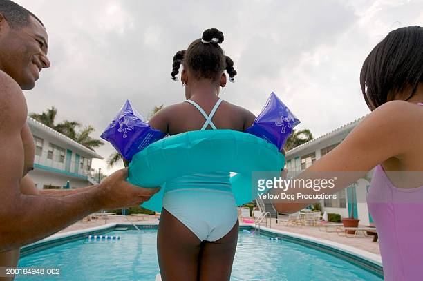 Parents holding girl (4-6) with inner tube on diving board