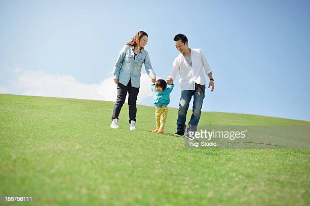 Parents holding hands with daughter
