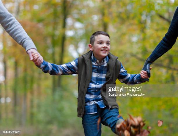 parents holding hands with son in autumn woods - family with one child stock pictures, royalty-free photos & images