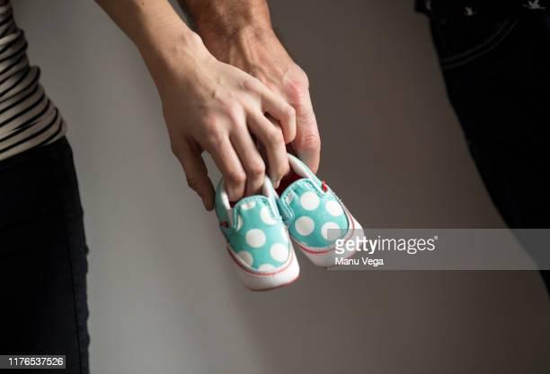 parents holding their baby's shoes on dark background. stock photography - casal chuveiro imagens e fotografias de stock