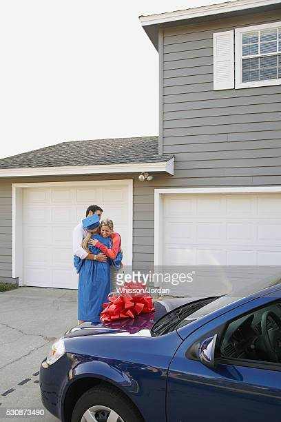 Parents hugging graduate with new car