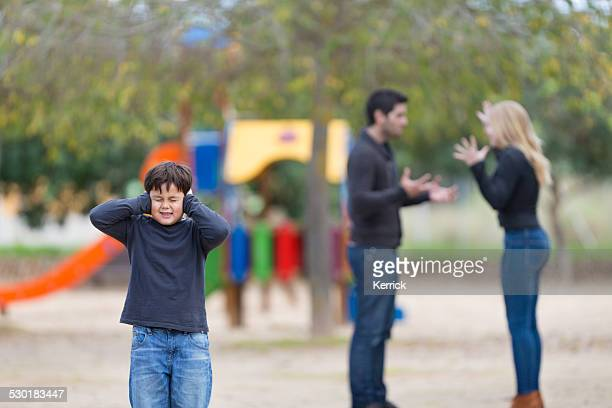 parents in conflict at playground with young boy