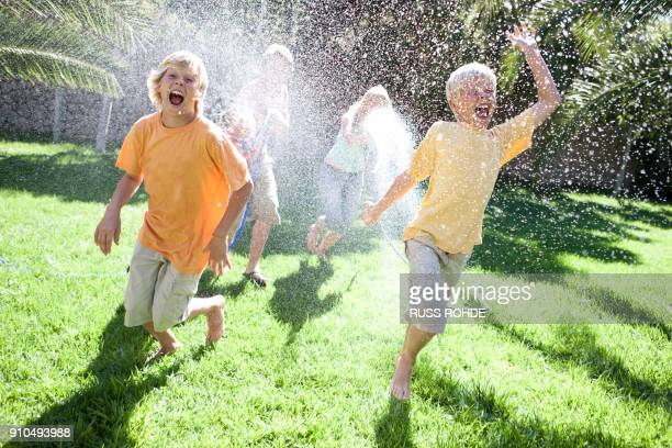 Parents in garden spraying sons with water from hosepipe