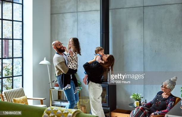 parents in living room with children and grandmother - mixed race person stock pictures, royalty-free photos & images