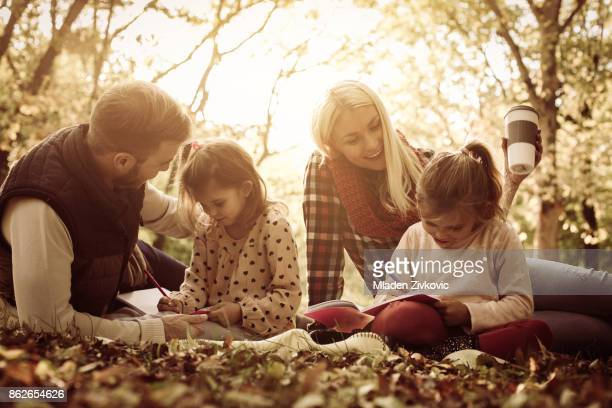 Parents in park with their daughters having education and teaching daughters to writing.