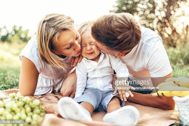 parents kissing boy sitting on field - one animal stock pictures, royalty-free photos & images