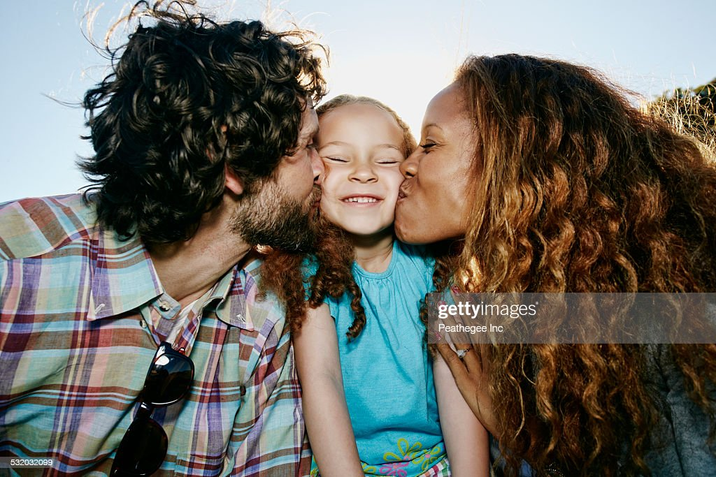 Parents kissing cheeks of daughter outdoors : Stock Photo