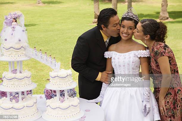 Parents kissing daughter at quinceanera