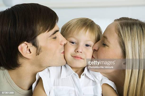 parents kissing little boy's cheeks, boy looking at camera - femme entre deux hommes photos et images de collection