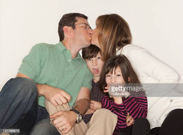 parents kissing with kids in the middle - couple tongue kissing stock photos and pictures