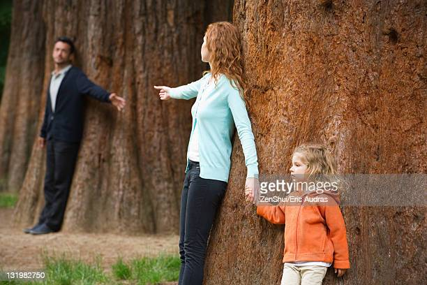 Parents leaning against separate trees, reaching out for each other