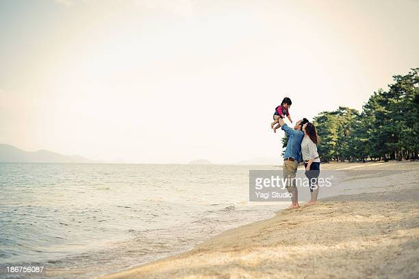Parents lifting daughter mid air on beach