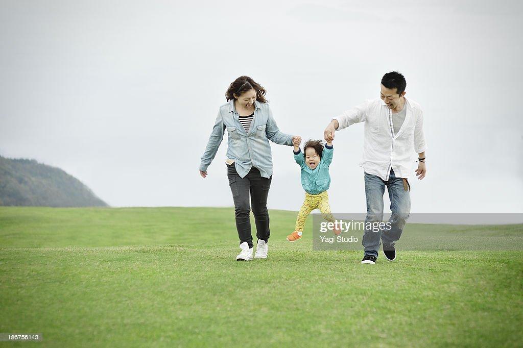 Parents lifting daughter mid air : Stock Photo