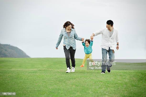 parents lifting daughter mid air - femme entre deux hommes photos et images de collection