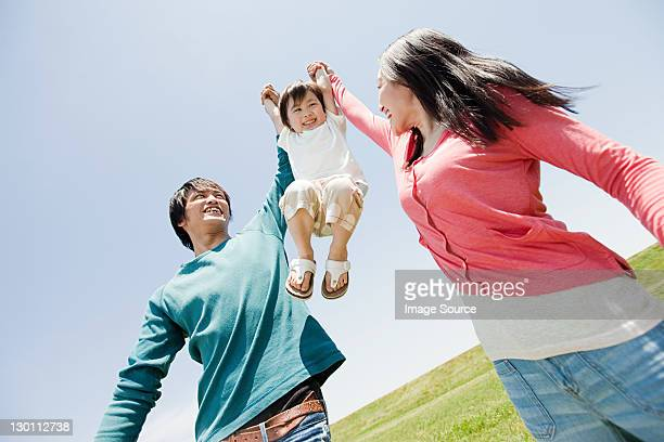 parents lifting son mid air - japan mom and son stock photos and pictures