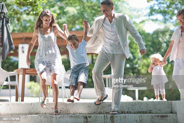 Parents lifting son over steps