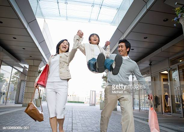 Parents lifting up son (6-7) in shopping mall