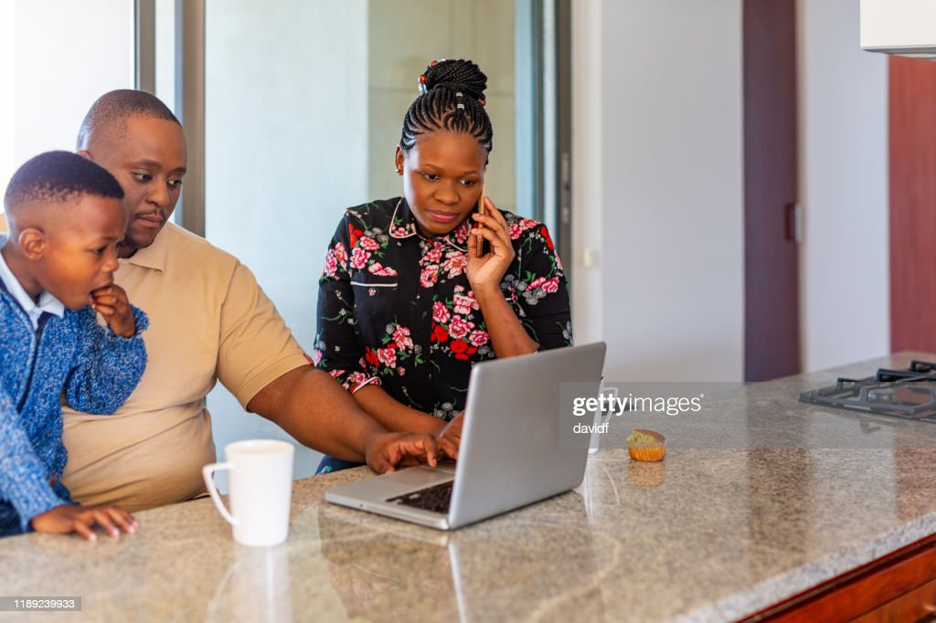 Parents Looking at a Laptop Computer at Home With Their Son : Stock Photo