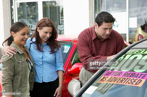 Parents looking at car on forecourt with daughter, smiling