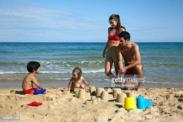 parents looking at children building sandcastle - petite fille culotte photos et images de collection