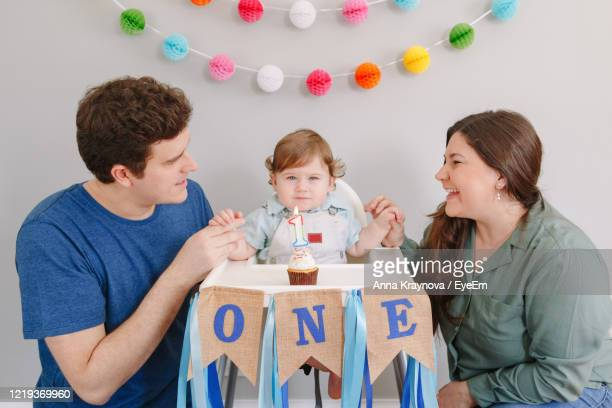 parents looking at cute baby boy with birthday cake sitting on high chair - happy birthday canada stock pictures, royalty-free photos & images