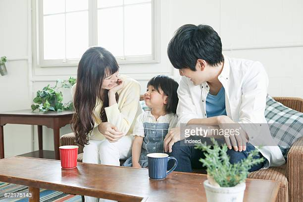 Parents looking at daughter on couch