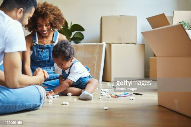 parents looking at daughter playing in new house - home ownership stock pictures, royalty-free photos & images