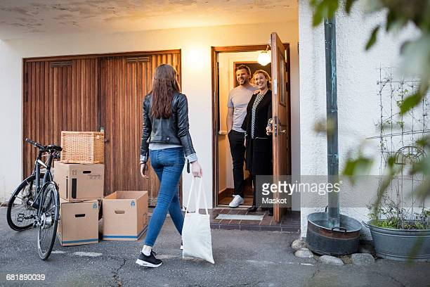 parents looking at daughter walking by cardboard boxes and bicycle outside house - rear view stock pictures, royalty-free photos & images