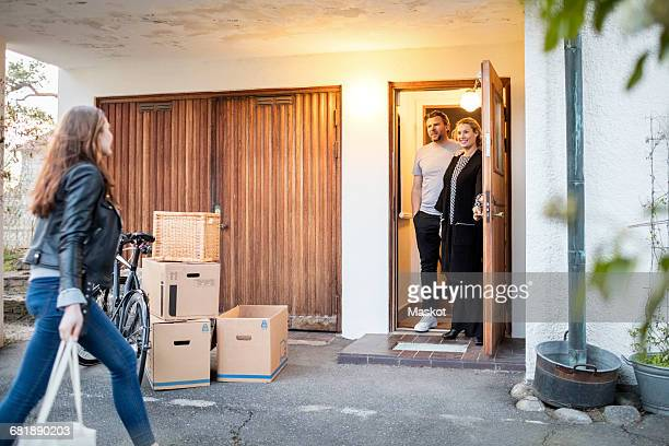 Parents looking at daughter walking by cardboard boxes and bicycle outside new house