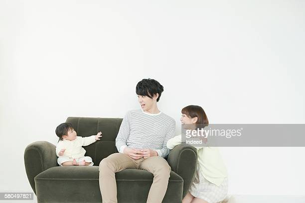 Parents looking at sitting baby on sofa