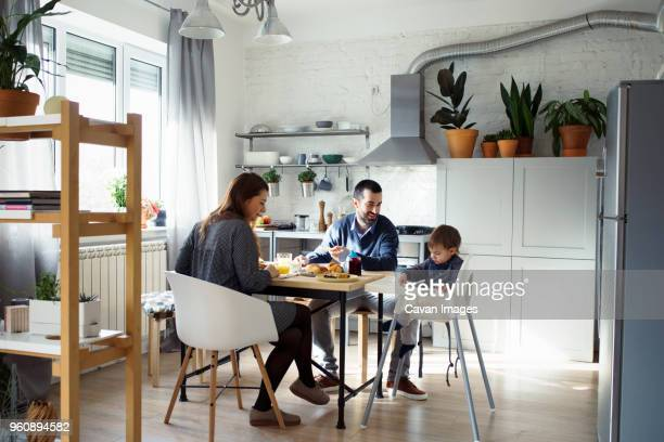 parents looking at son sitting on high chair while having breakfast in kitchen - simple living stock pictures, royalty-free photos & images
