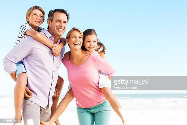 parents looking away while piggybacking children on beach - four people stock pictures, royalty-free photos & images