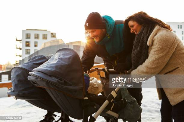 parents looking inside pram - paternity leave stock pictures, royalty-free photos & images