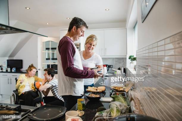 parents making lunch while son cares for disabled daughter - danish food stock pictures, royalty-free photos & images