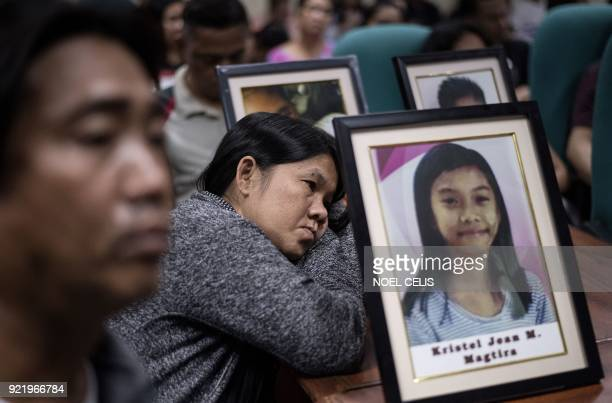 TOPSHOT Parents of children injected with Dengvaxia vaccine carry pictures of their loved ones as they attend a senate hearing regarding the vaccine...