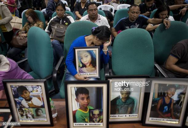 Parents of children injected with Dengvaxia vaccine carry pictures of their loved ones as they attend a senate hearing regarding the vaccine at the...