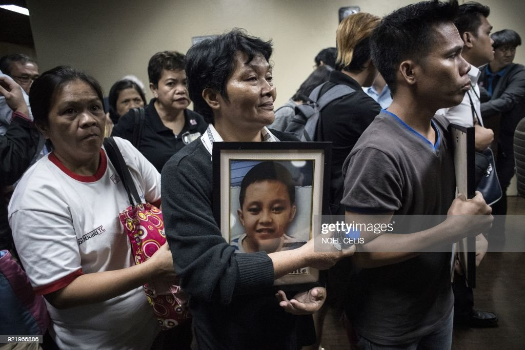 Parents of children injected with Dengvaxia vaccine carry pictures of their loved ones as they attend a senate hearing regarding the vaccine at the Senate building in Manila on February 21, 2018. Widespread fears over a controversial dengue vaccine that some families blame for child deaths is wreaking havoc on the Philippines' war on disease, with parents unwilling get their kids protection from other ailments, a senior health official said February 2. /