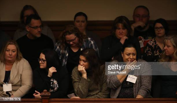 Parents of children with autism listen to Todd Smith, the Minister of Children, Community and Social Services answer a question at Queens Park as the...