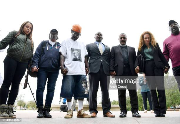 Parents of Elijah McClain Sheneen McClain second from left and LaWayne Mosley third from left hold hands and pray with local pastors family friends...