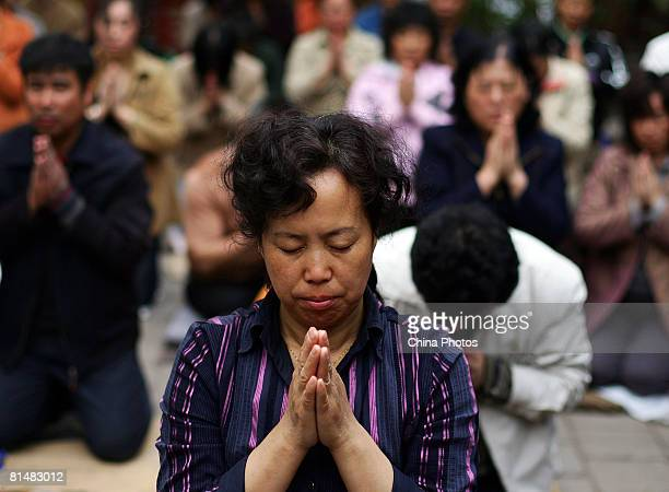 Parents of highschool graduates pray while their children take the National College Entrance Examination during a buddhist ceremony at the Yuhuangge...