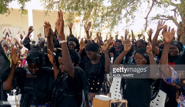 Parents of the missing Chibok schoolgirls raise their hands as they pray for the release of their daughters kidnapped by Boko Haram jihadists during...
