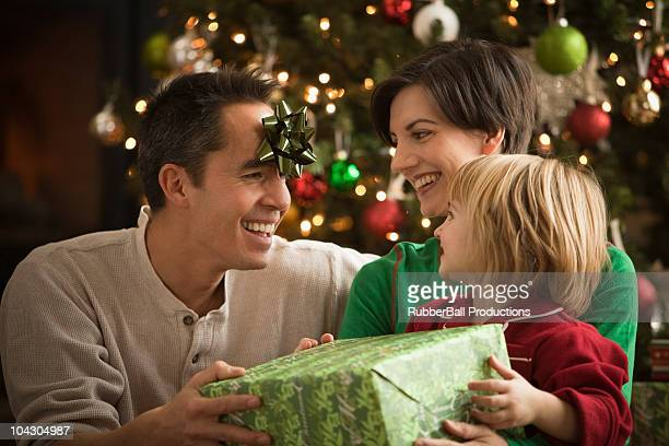 parents opening presents with their young child - orem utah stock pictures, royalty-free photos & images