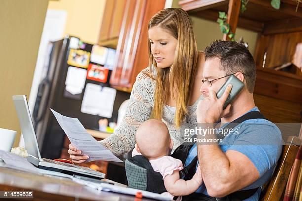 Les Parents rendant Hôpital factures tout en prenant soin de bébé fille