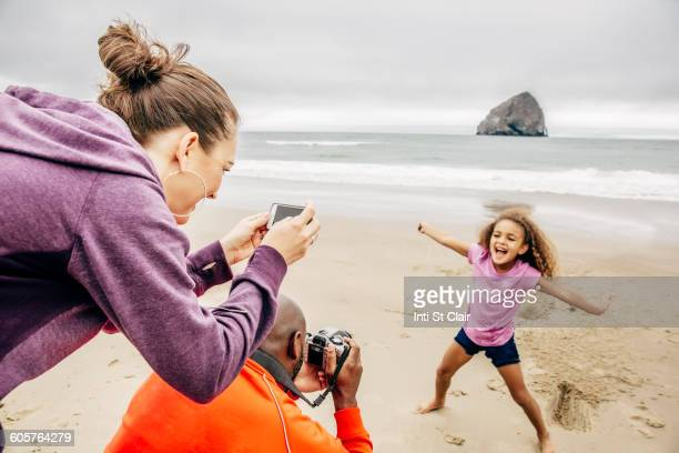 parents photographing daughter on beach - camera girls stock photos and pictures